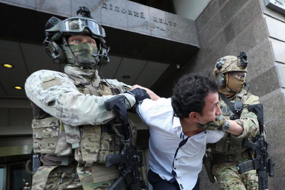 Bewaffnete Polizeibeamte halten den Mann fest, der im Zentrum der ukrainischen Hauptstadt kurzzeitig gedroht hat, eine Bankfiliale zu sprengen.