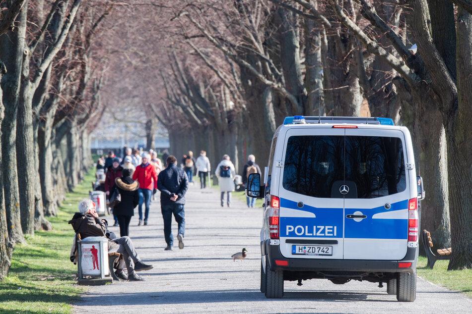 Zahlreiche Menschen gehen am Maschsee spazieren, während Polizisten aus einem Fahrzeug die Menschen dazu aufrufen, den Mindestabstand von 1,5 Metern einzuhalten.