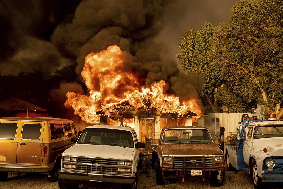 """Flammen des """"Sugar Fire"""" schlagen aus einem Wohnhaus, vor dem zahlreiche Fahrzeuge stehen. Der Westen der USA hatte am Wochenende nicht nur mit enormer Hitze, sondern auch mit Waldbränden zu kämpfen."""