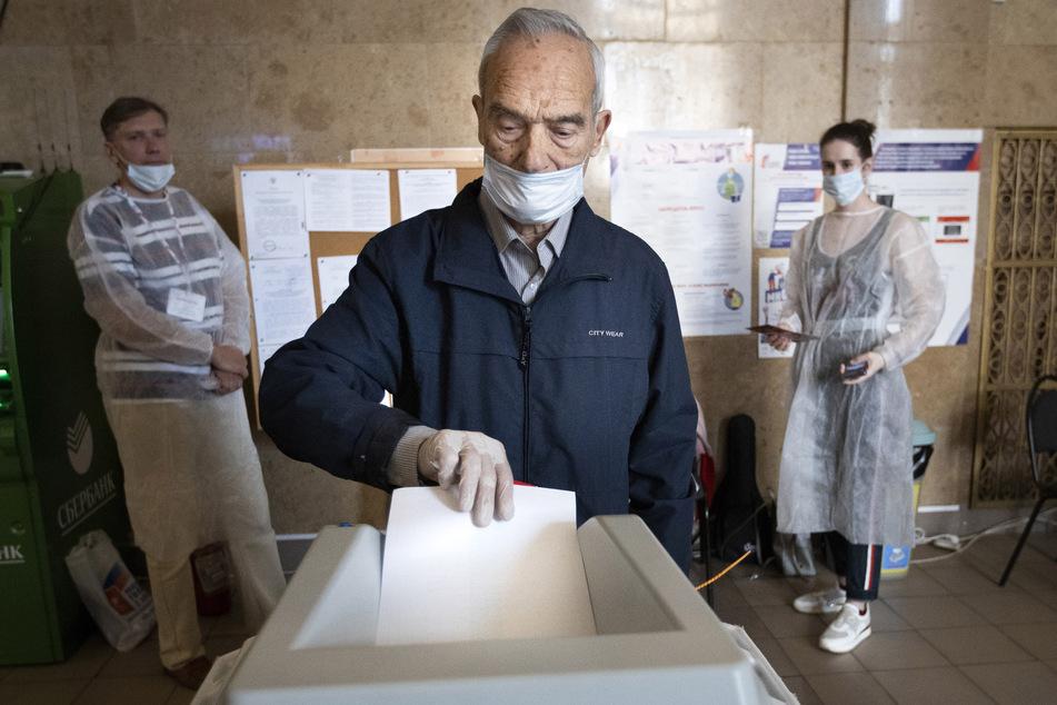 Ein Wähler, der einen Mundschutz und Handschuhe zum Schutz vor dem Coronavirus trägt, wirft seinen Stimmzettel in einem Wahllokal in Moskau in eine Wahlurne. Bis Mittwoch, den 1. Juli, konnten die Menschen über eine Verfassungsänderung abstimmen, die Präsident Putin dauerhaft die Macht sichern soll.