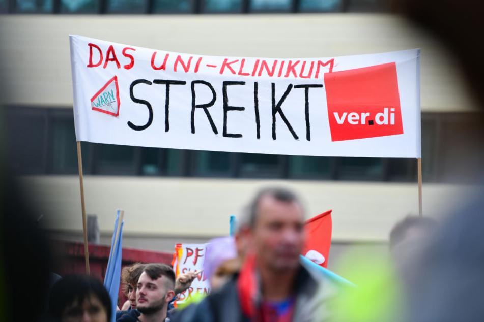 """Teilnehmer halten bei einer Kundgebung vor dem Neubau der Chirurgie des Universitätsklinikums ein Transparent mit der Aufschrift """"Das Uni-Klinikum streikt"""" in die Höhe."""