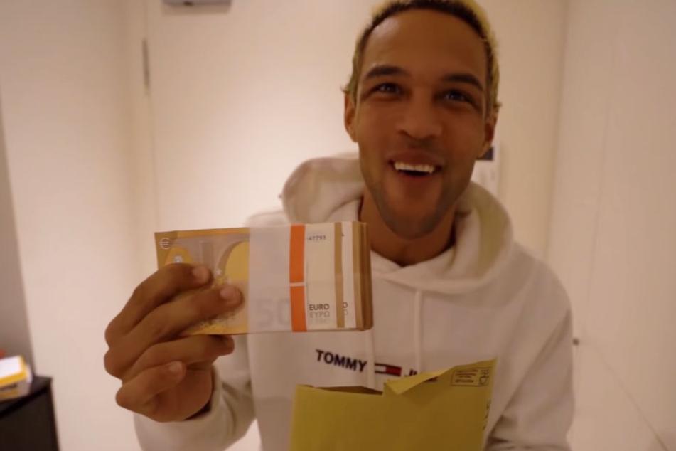Simon Desue nimmt den Umschlag mit dem Falschgeld in Empfang.