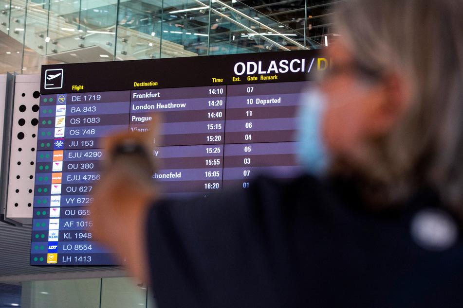 Kroatien, Split: Ein Reisender zeigt auf eine Tafel mit den Abflugzeiten im internationalen Flughafen.