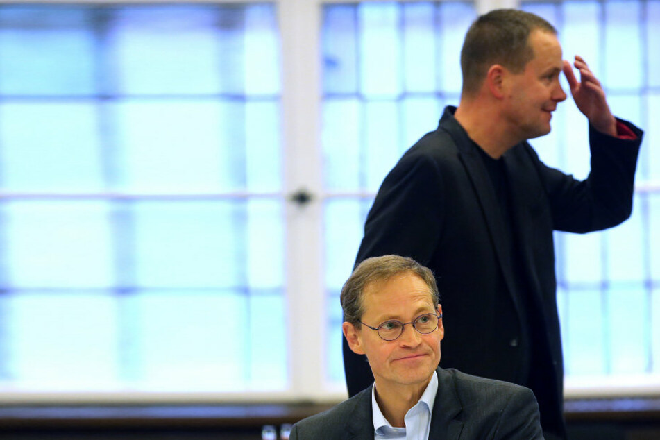 Der Regierende Bürgermeister Michael Müller (SPD) im Oktober zu Beginn der rot-rot-grünen Koalitionsgespräche im Roten Rathaus in  Berlin am Verhandlungstisch, während Klaus Lederer (Linke) hinter ihm vorbei  geht.