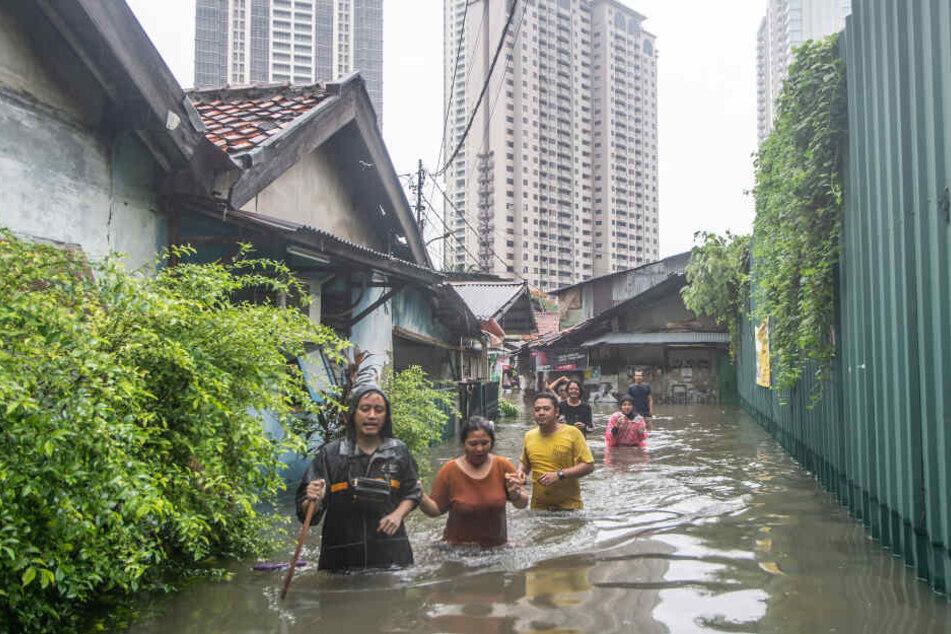 Menschen gehen auf einer vom Hochwasser überfluteten Straße.
