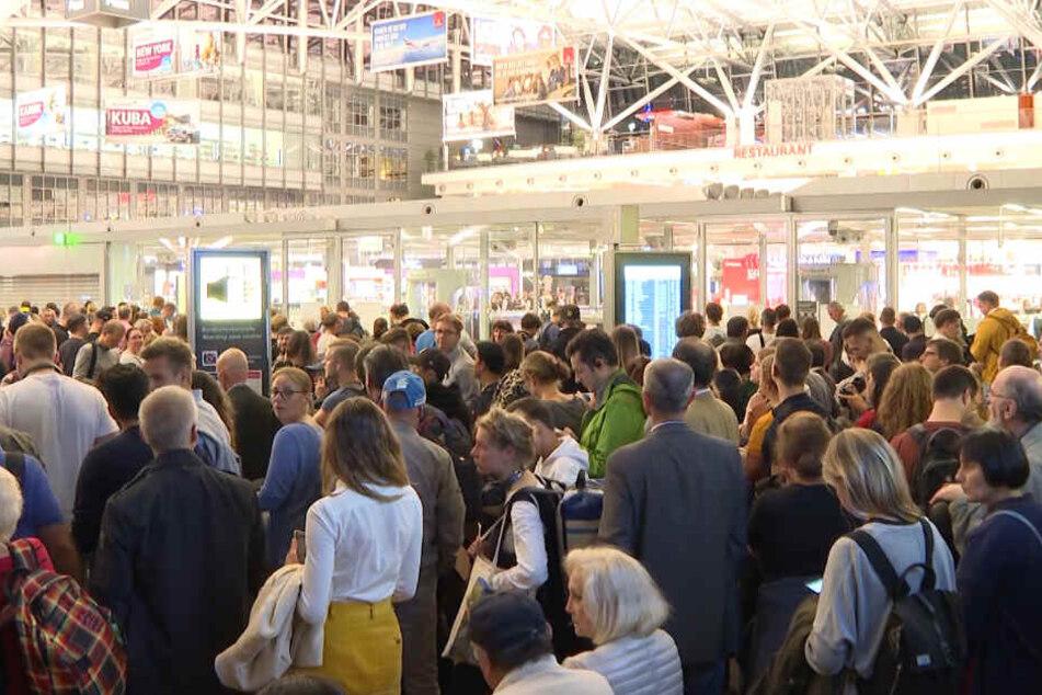 Zahlreiche Passagiere stehen im Hamburger Flughafen.