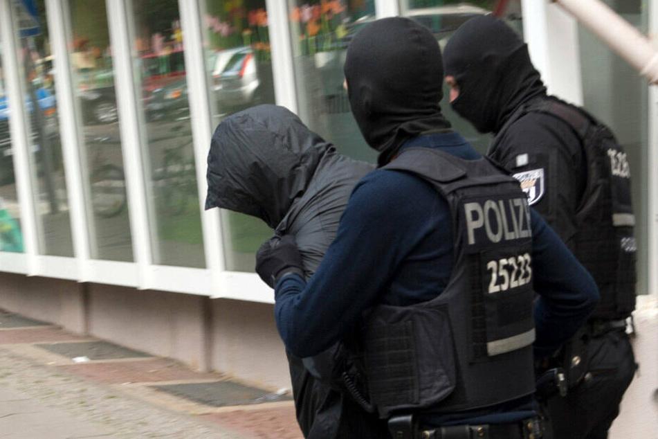 Polizeibeamte führen einen Mann ab. Dreieinhalb Monate nach dem spektakulären Diebstahl einer 100-Kilo-Goldmünze aus dem Berliner Bode-Museum im März 2017 hat die Polizei zwei Verdächtige festgenommen. (Archivbild)