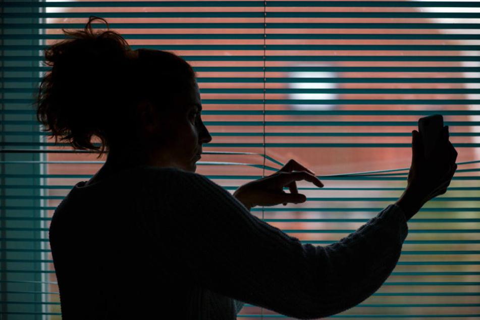 Eine Frau beobachtet durch eine geschlossene Jalousie nach einem Stalking-Anruf die Straße vor ihrem Haus. (Symbolbild)