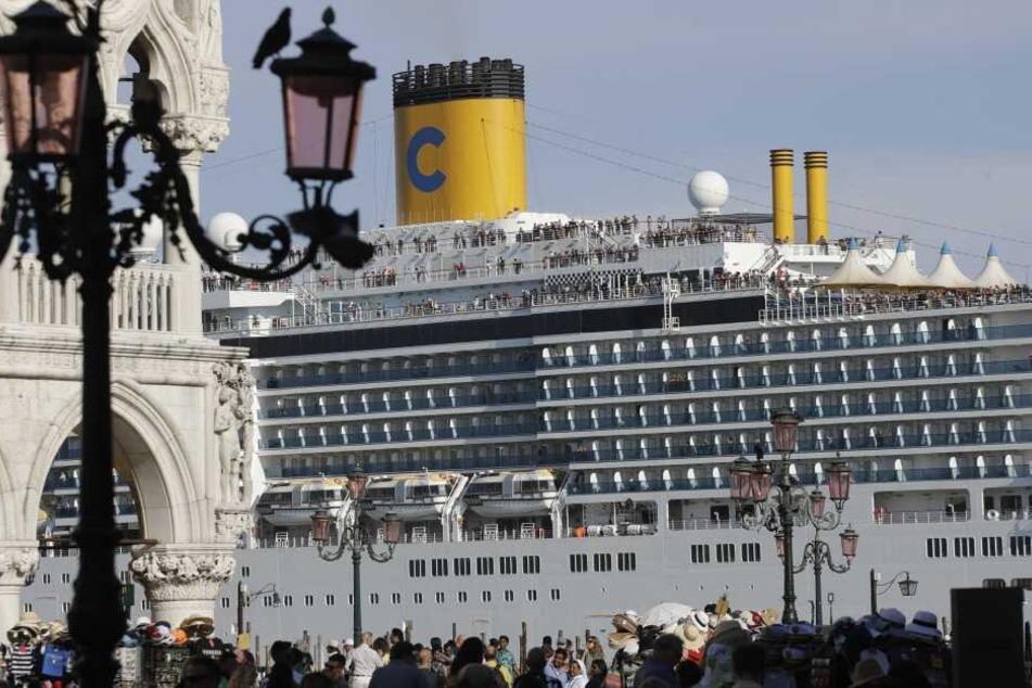 """Das Kreuzfahrtschiff """"Costa Deliziosa"""" fährt am Markusplatz vorbei, auf dem zahlreiche Touristen unterwegs sind. Im Streit um Kreuzfahrtschiffe in Venedig will der Bürgermeister die Unesco auffordern, die Stadt auf die Rote Liste des gefährdeten Weltkultu"""