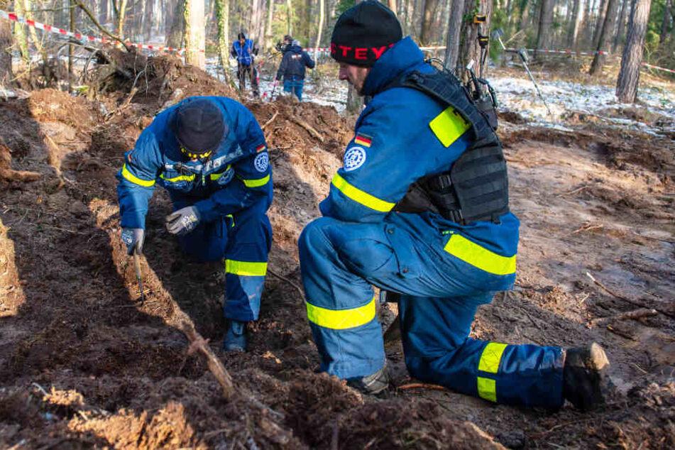 Zwie Helfer des Technischen Hilfswerks (THW) untersuchen den Boden in einem Waldstück, in dem die Polizei nach der Leiche der vermissten Katrin Konert gegraben hat.