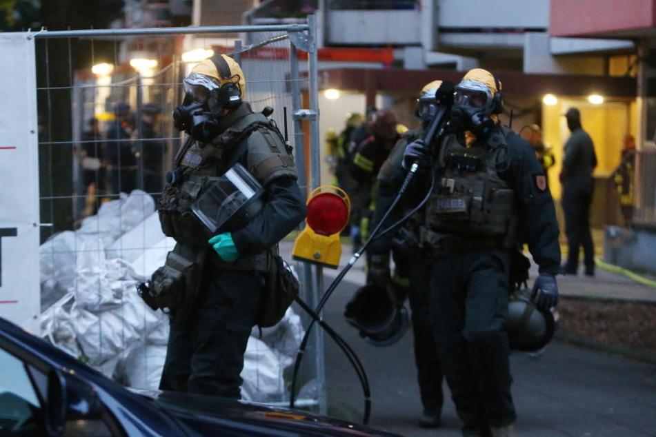 SEK Beamte mit Atemschutzmasken und Schutzanzügen verlassen das Hochhaus in Chorweiler.