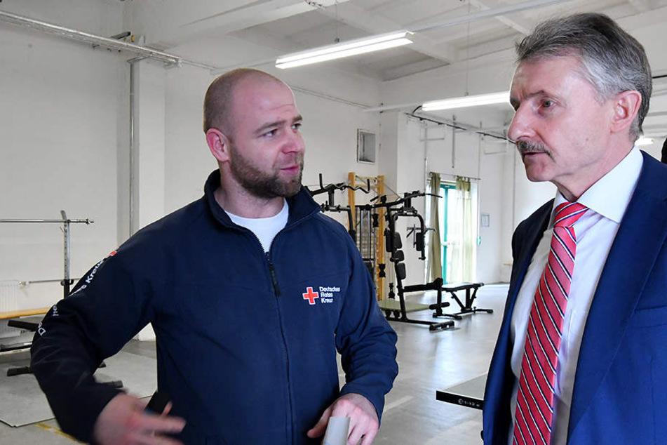 Brandenburgs Innenminister Karl-Heinz Schröter (SPD) unterhält sich mit Fitnesstrainer Rene Schenk, der in der Einrichtung arbeitet.