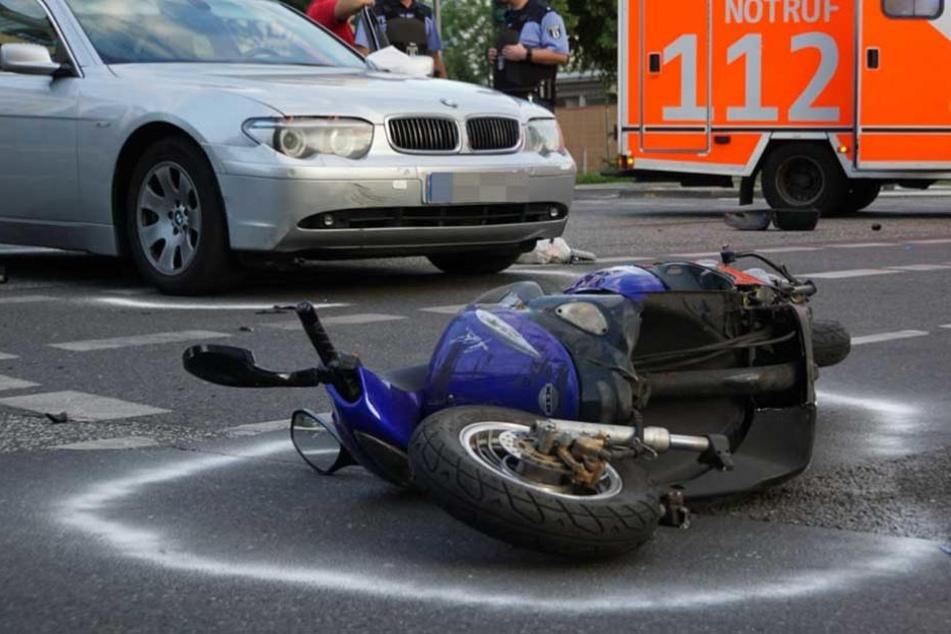 Der völlig demolierte Motorroller liegt auf der Straße.