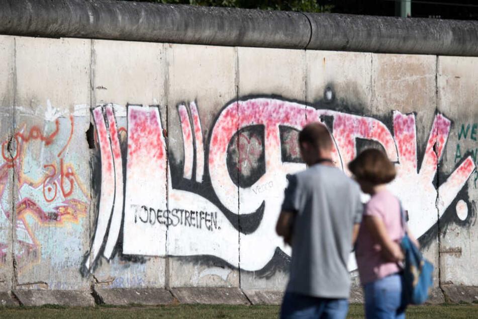 Touristen besichtigen auf dem Gelände der Gedenkstätte Berliner Mauer.