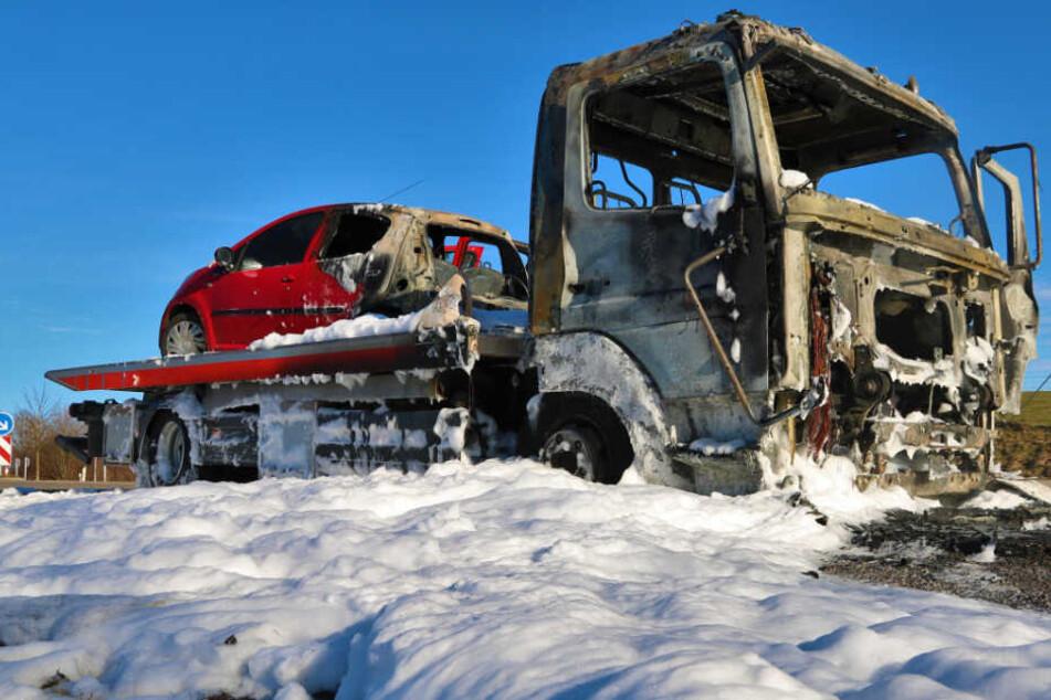Das ausgebrannte Auto steht auf der Ladefläche des ebenfalls ausgebrannten Abschleppwagens.
