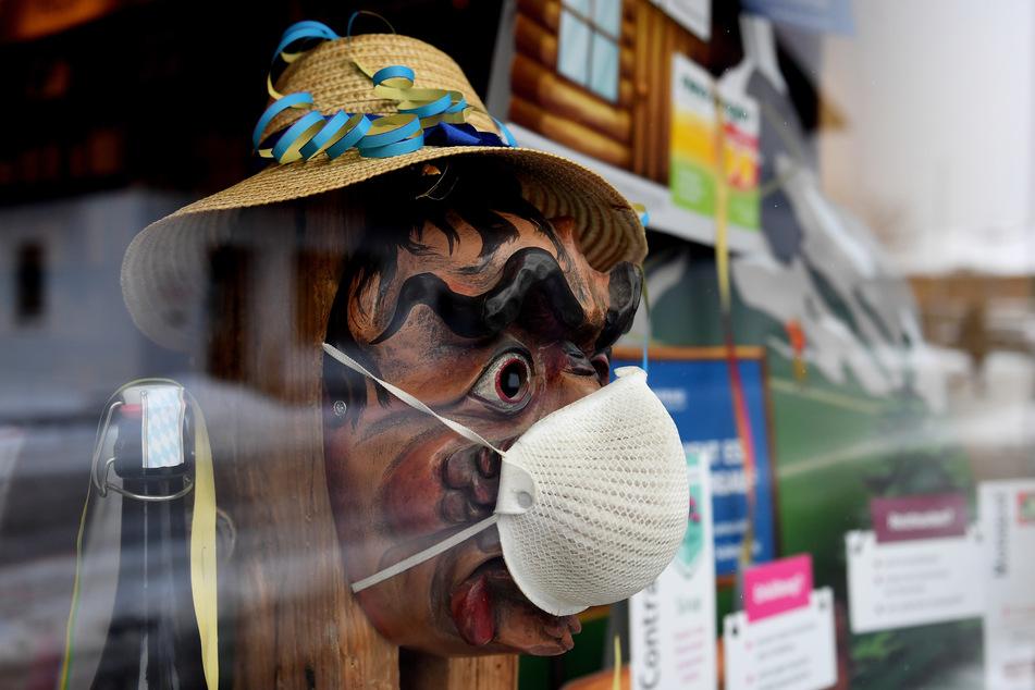 Im Schaufenster einer Apotheke trägt eine Holzlarve, die sonst Einheimische beim traditionellen Maschkera-Gehen tragen, eine FFP2-Maske. Zuhause bleiben heißt es für Hexen, Gnome und andere Faschingsgestalten.