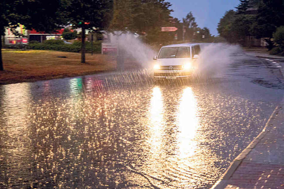 In Bischofswerda bahnt sich ein Fahrzeug den Weg durch die Wassermassen.
