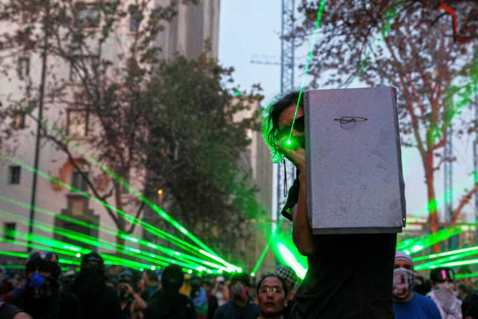 Demonstranten zielen bei einer Demonstration mit Laserpointern auf die Polizei.