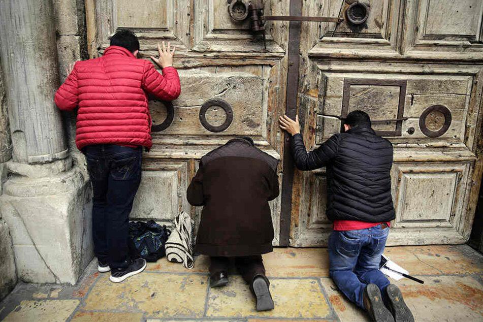 Besucher beten vor der geschlossenen Tür der Grabeskirche, der heiligsten Stätte des Christentums, in der Altstadt von Jerusalem.