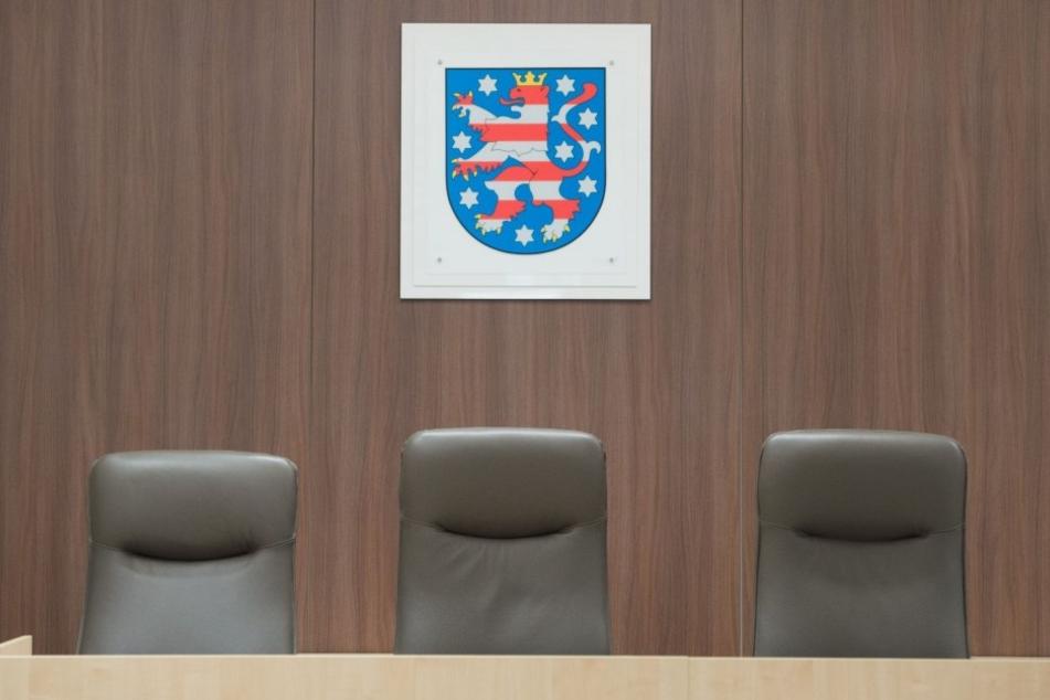 Drei Stühle stehen im Landgericht in Gera (Thüringen) vor dem Landeswappen.
