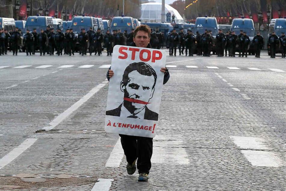 Ein Demonstrant mit einem Plakat mit dem Abbild des französischen Präsidenten geht auf der Champs Elysees, im Hintergrund stehen Polizisten.