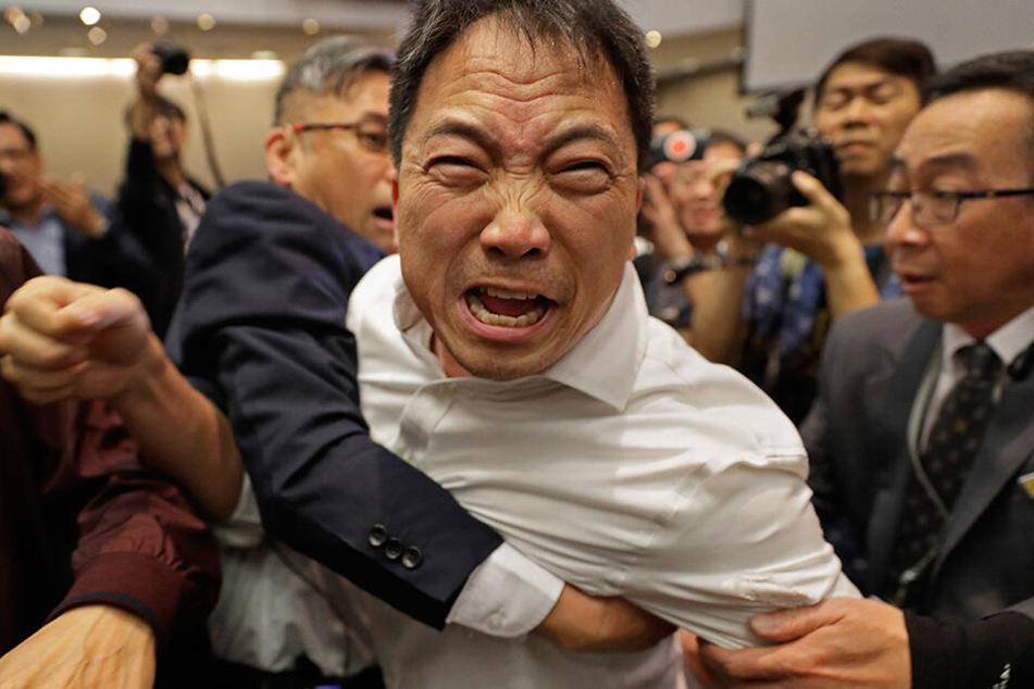 Sicherheitspersonal hält den Abgeordneten des demokratischen Lagers, Wu Chi-wai (M), bei einem Streit mit Pro Chinesischen Abgeordneten im Parlament, dem Legislativrat der Sonderverwaltungszone Hong Kong, fest.