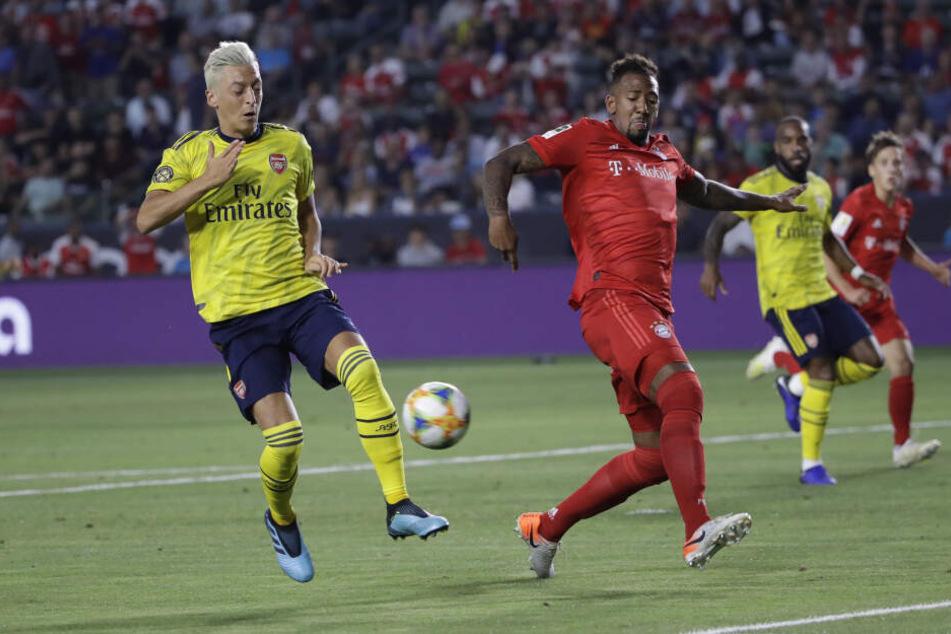 Münchens Jerome Boateng (r) gegen Arsenals Mesut Özil.