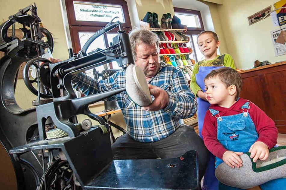 Manfred Seidel (68) zeigt seinen Enkeln Martin (2) und Johann (5) die etwa 100 Jahre alte Nähmaschine. Dort werden Filzpantoffel von Hand gefertigt.