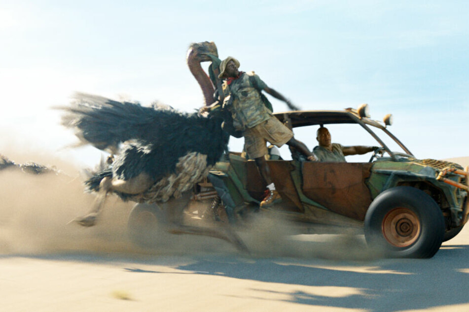 Dr. Smolder Bravestone (r., Dwayne Johnson) rettet Moose Finbar (Kevin Hart) aus den Fängen von einem angriffslustigen Afrikanischen Strauß.