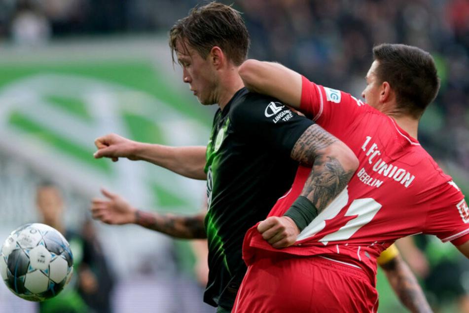Wolfsburgs Torschütze Wout Weghorst (l.) und Keven Schlotterbeck kämpfen um den Ball.