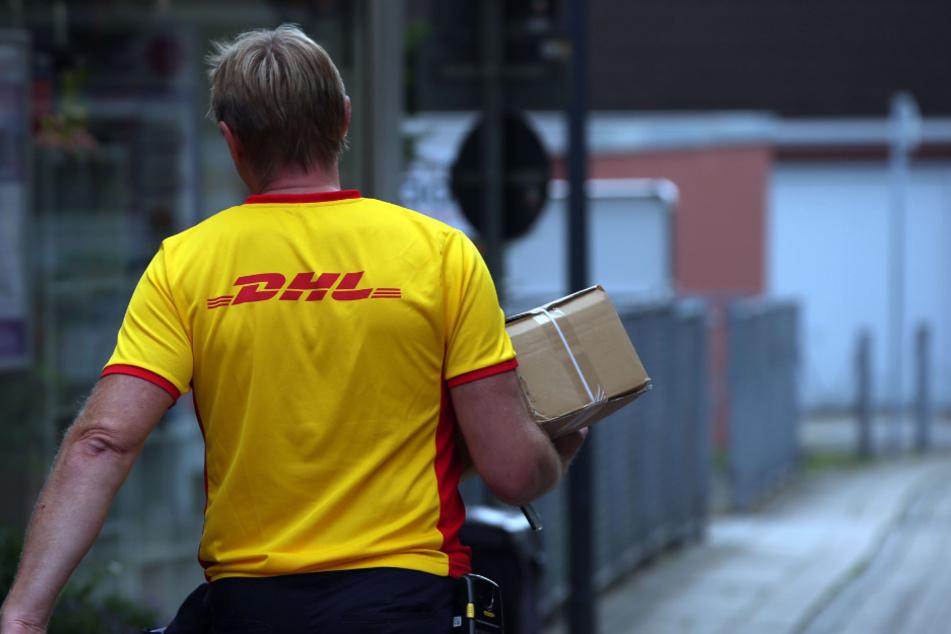 Ein Paketzustellerder von Deutsche Post DHL liefert ein Paket aus.