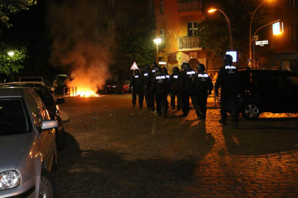 Polizisten nähern sich den brennenden Barrikaden