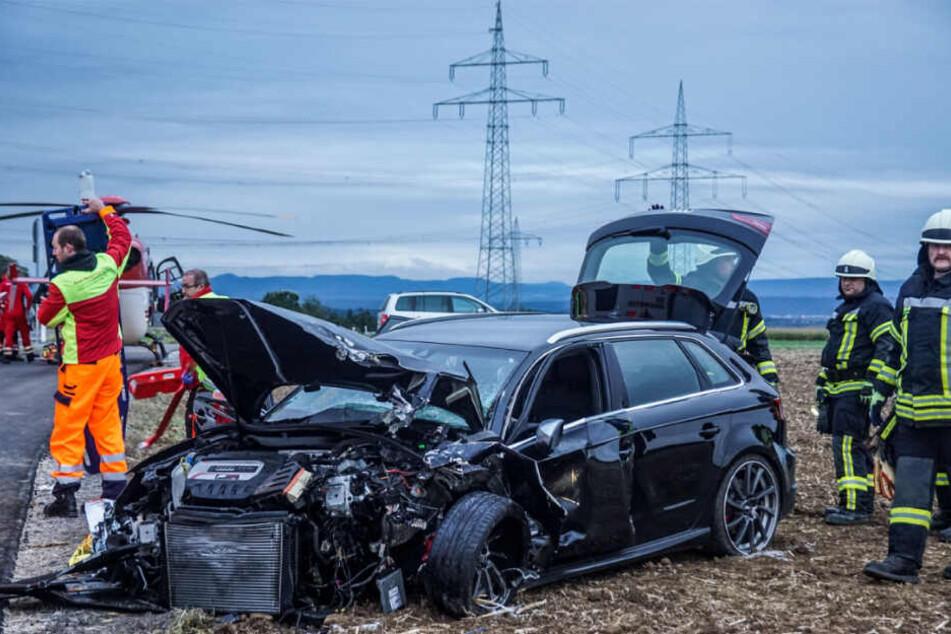 Rettungskräfte vor dem verunfallten Wagen.