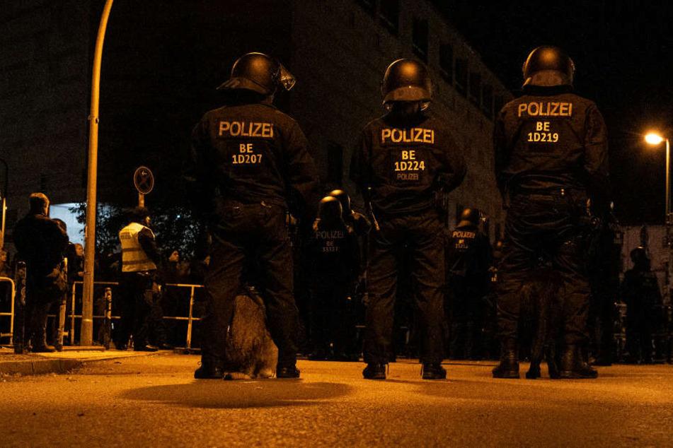 Polizeibeamte mit Hunden stehen unweit der Rigaer Straße Demonstranten gegenüber, die gegen eine Veranstaltung der rechts gerichteten Vereinigung Pegida aus München protestierten.