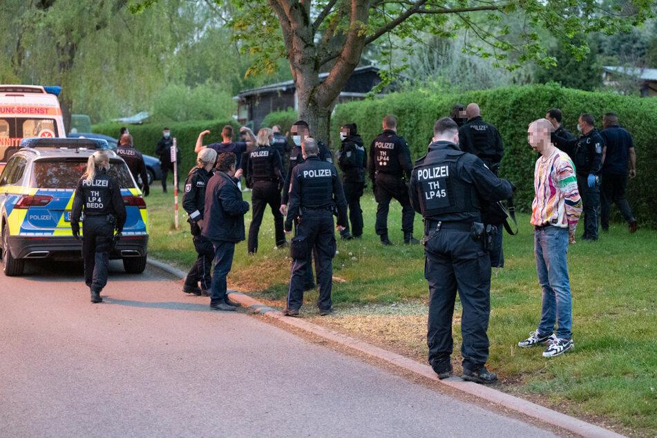 Mehrere Polizeibeamte stehen vor der Gartenanlage und befragen Personen.