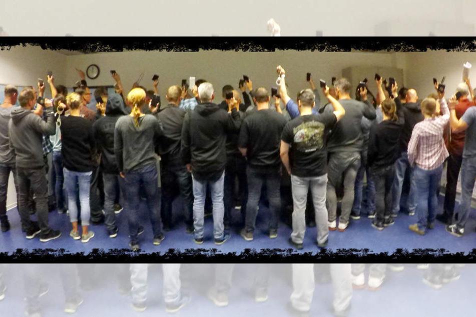Handschellen, Smartphones und eine Zeitung halten die eingesetzten Ermittler beim gemeinsamen Rücken-Gruppenfoto hoch.