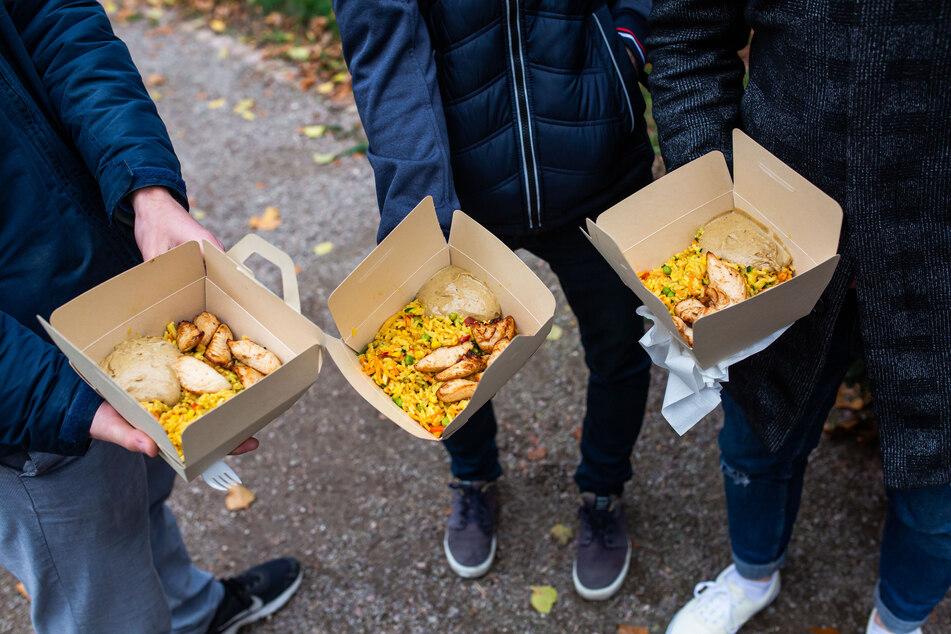 Drei Studenten stehen mit Ihrem Essen in einer Papierbox auf einer Straße.
