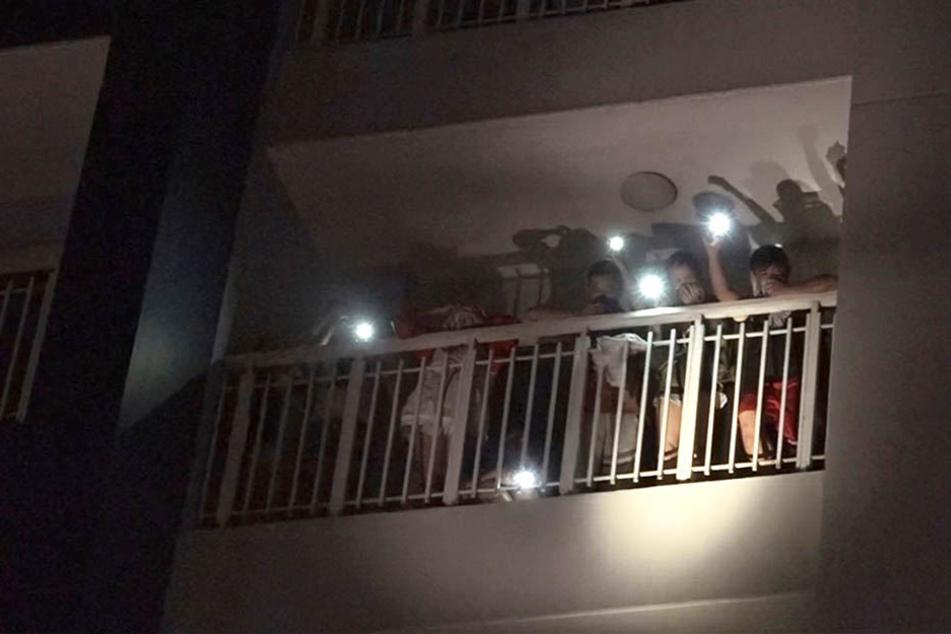 Bewohner eines Wohnkomplexes rufen mit den Lichtern ihrer Mobiltelefone um Hilfe nach dem Aubruch eines Feuers.