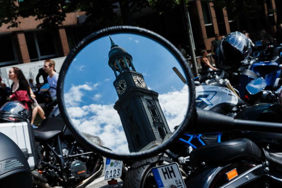 Motorräder und Fahrer, die am diesjährigen Motorradgottesdienst MoGo teilnehmen, stehen vor der Hauptkirche St. Michaelis in Hamburg.