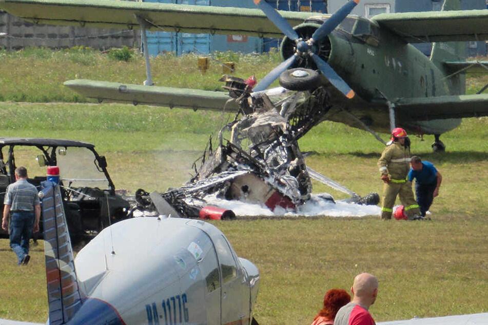 Die Trümmer eines Doppeldeckerflugzeuges vom Typ Antonow An-2 liegen auf den Flugplatz.