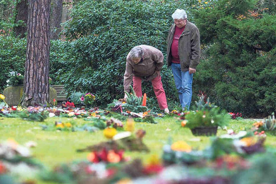 Monika (67) und Herbert Kirsch (69) legen einen Kranz für die verstorbene Großmutter an den Rand der grünen Wiese. Eigentlich ist ihr Grab ein paar Schritte weiter in der Mitte - aber dorthin dürfen sie nicht zu Fuß.