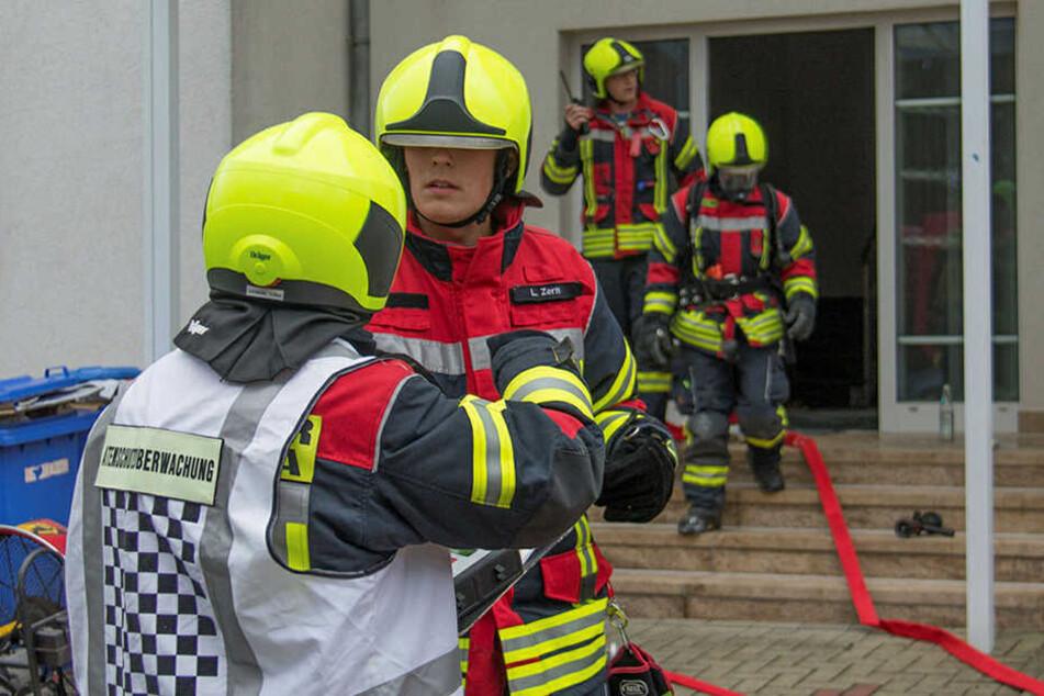 Feuerwehrmänner versorgten die Frau, nachdem diese brennend aus dem Haus rannte.