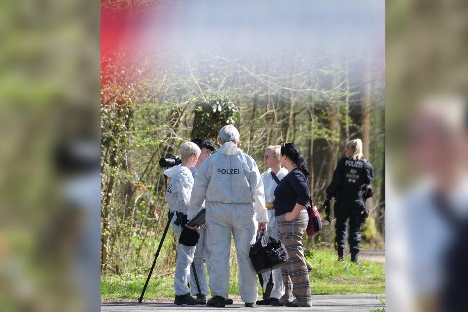 Beamte der Spurensicherung besprechen mit einer Ermittlern am Tatort das weitere Vorgehen.