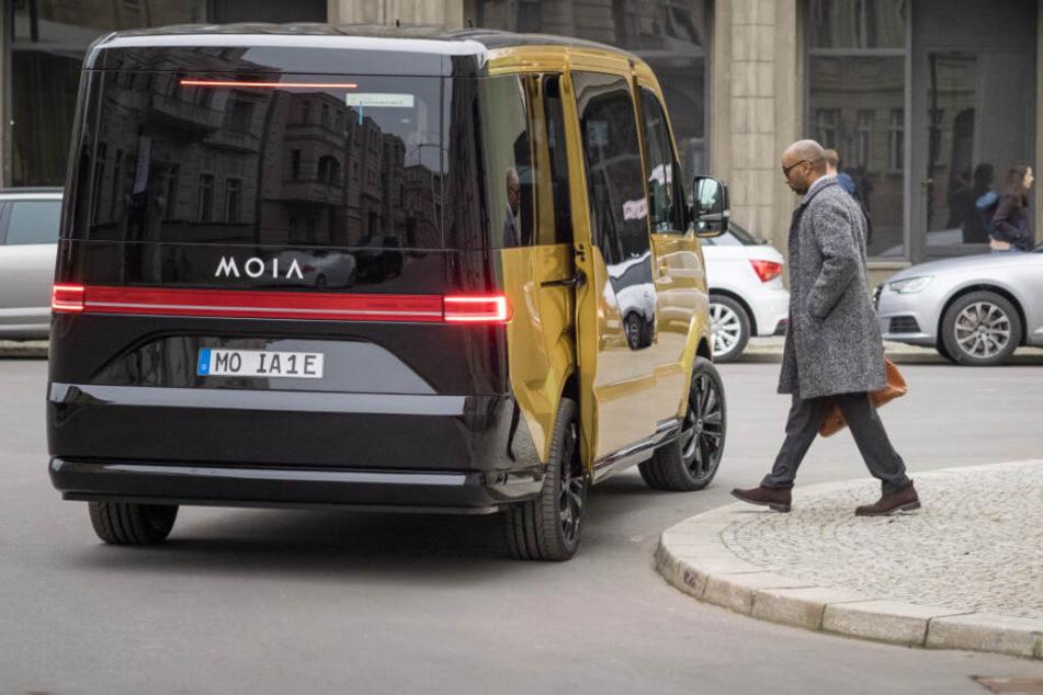 Ein Moia-Elektrobus sammelt einen Passagier in der Innenstadt ein.