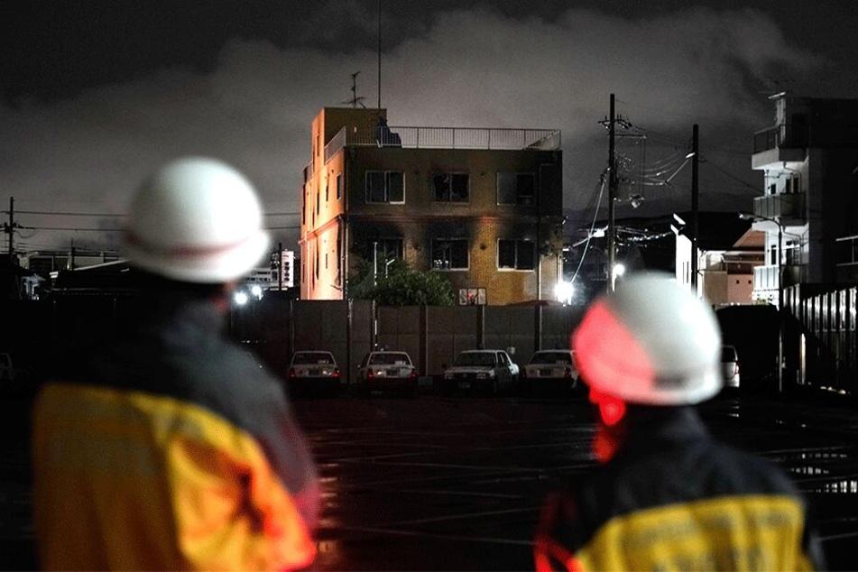 Zwei Feuerwehrleute schauen auf das ausgebrannte Gebäude nach dem Anschlag auf das berühmte Animationsstudio im japanischen Kyoto.