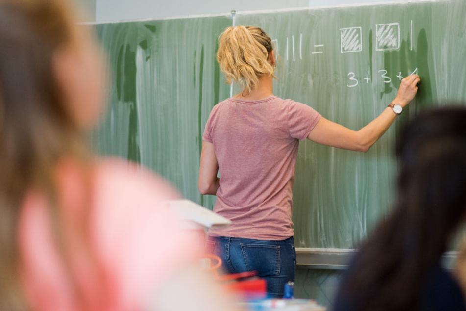 Eine junge Lehrerin schreibt an eine Schultafel im Mathematikunterricht einer 8. Klasse an einer Integrierten Gesamtschule.