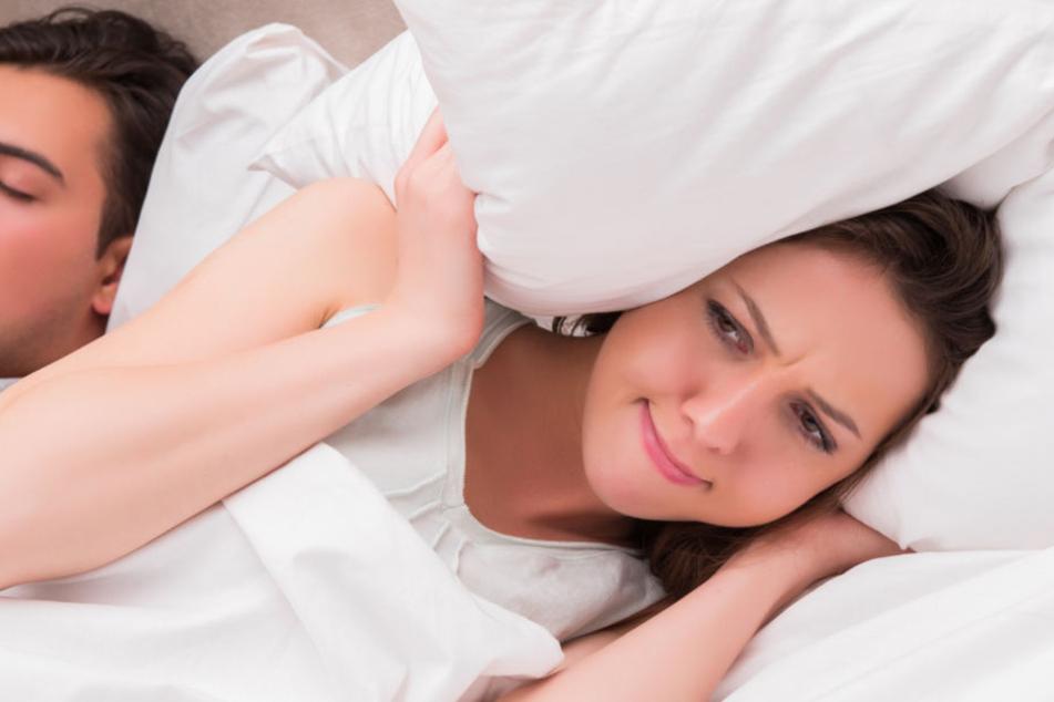 Eine Frau hält sich mit einem Kissen die Ohren zu. (Symbolbild)