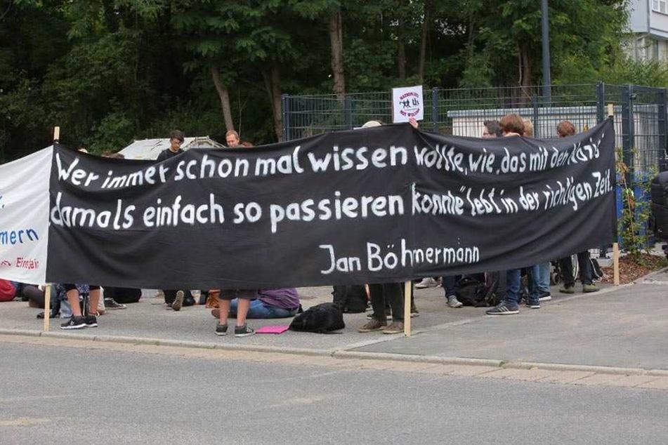 Protestierende halten ein Banner nach oben.