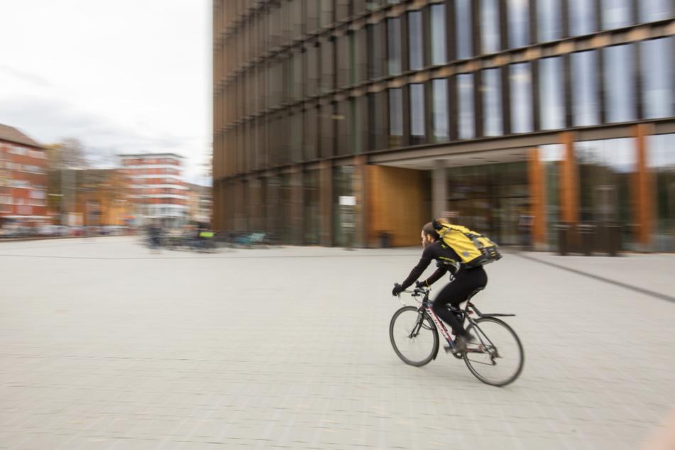 Ein Fahrradkurier fährt vor dem Freiburger Rathaus im Stühlinger entlang.