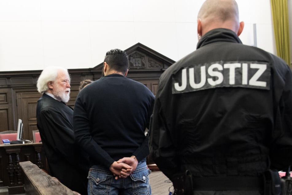 Zu Prozessbeginn steht der Angeklagte (Mitte) neben seinem Anwalt im Gerichtssaal.
